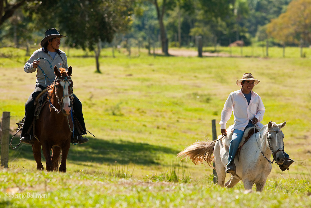 Cowboys happily return after a long days work on thier cattle ranch in the Bolivian Amazon.