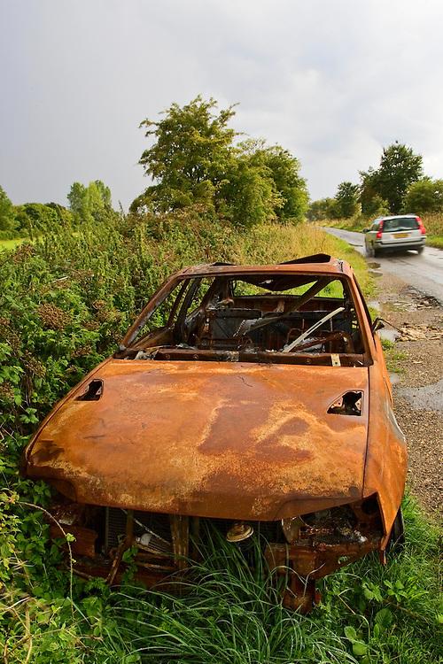 Burnt-out car wreck on roadside, Oxfordshire, United Kingdom