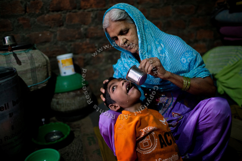 Bano Bi Ali, 70, is feeding her grandson Rahil Ali, 7, a boy suffering from a severe neurological disorder, in their home in Bhopal, Madhya Pradesh, India, near the abandoned Union Carbide (now DOW Chemical) industrial complex. Rahil lives with his father, Rashid Ali, 35, and his mute and deaf grandmother, in a small, single room his father rents inside a larger house. Rahil's mother left the family three years ago, his father says, because of the hardship and stigma associated to birth defects in India. She took with her Rahil's two siblings, a sister now aged 6 and a brother aged 3, and remarried. In the past, Rashid and his now ex-wife had no choice but to feed the family on contaminated water for a period about six years, in which all three children were born. But while his siblings appear to be healthy to this day, Rahil was diagnosed with torch infection and Lissencephaly after a CT scan was made of his brain soon after his birth. The latter disorder is incurable, and children in similar conditions to Rahil's have a average life expectancy of less than ten years.