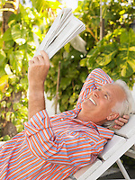 Man reclining on lounge chair reading newspaper side view