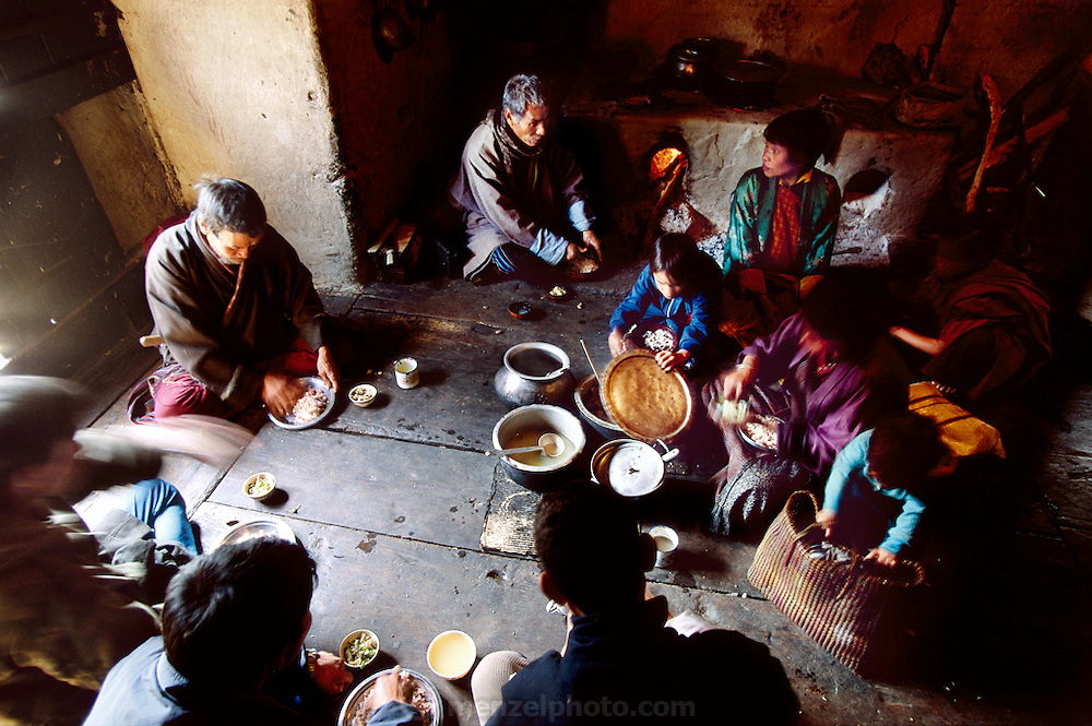 (MODEL RELEASED IMAGE). Namgay (left, by fire) and his wife Nalim (right, by fire) eat a lunch of red rice and a small cup of cooked vegetables with their family and friends in the kitchen area of their earth-walled house in Shingkhey, a remote village in the mountains of Bhutan. The kitchen and adjoining rooms are often smoky because the cookstove/fireplace is inside the house and doesn't vent to the outside. Nalim says that she would like to build a kitchen in a different building but can't afford it. Hungry Planet: What the World Eats (p. 39).