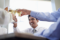 Business associates toasting with wine glasses close-up
