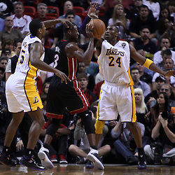 March 10, 2011; Miami, FL, USA; Miami Heat shooting guard Dwyane Wade (3) is defended by Los Angeles Lakers shooting guard Kobe Bryant (24) and small forward Ron Artest (15) during the first quarter at the American Airlines Arena.  Mandatory Credit: Derick E. Hingle
