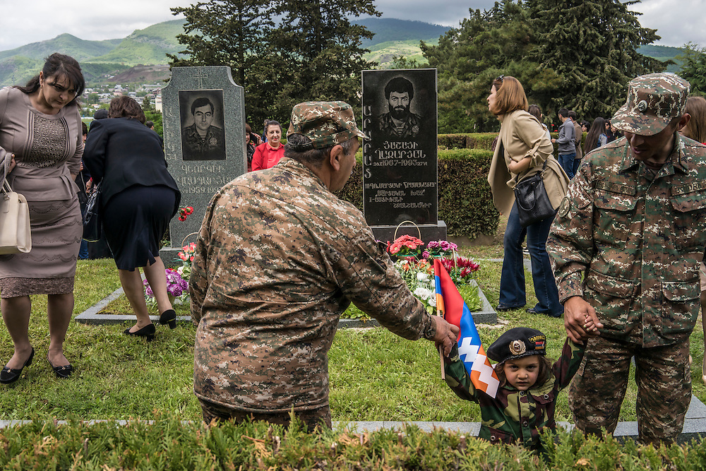Soldiers and civilians lay flowers at the graves of local fighters killed during the war in the 1990s between Armenia and Azerbaijan following a ceremony commemorating both the victory over Nazi Germany in the Second World War as well as the fall of the strategic town of Shushi to Armenian forces on Monday, May 9, 2016 in Stepanakert, Nagorno-Karabakh.