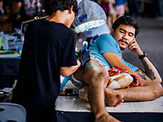 28 OCTOBER 2018 - BANGKOK, THAILAND: A man gets a tattoo on his thigh at the 2018 MBK Center Tattoo Fest. Tatoo artists from around the world came to participate in the festival, which featured both modern (using tattoo machines) and traditional methods (done by hand with long needles) of tattooing.     PHOTO BY JACK KURTZ