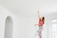 Full-length of woman on ladder fitting light bulb in new house