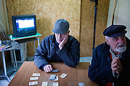 L'Aquila, Italia - 30 marzo 2013. Anziani giocano a carte in un container al centro della città..Ph. Roberto Salomone