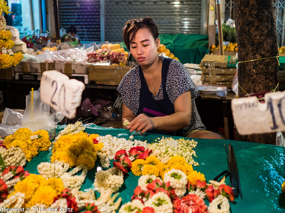 24 FEBRUARY 2016 - BANGKOK, THAILAND: A woman makes flower garlands in her sidewalk stall in front of Pak Khlong Talat in Bangkok. Bangkok government officials announced this week that vendors in Pak Khlong Talat, Bangkok's well known flower market, don't have to move out on February 28. City officials are trying to clear Bangkok's congested sidewalks and they've cracked down on sidewalk vendors. Several popular sidewalk markets have been closed in recent months and the sidewalk vendors at the flower market had been told they would be evicted at the end of the month but after meeting with vendors and other stake holders city officials relented and said vendors could remain but under stricter guidelines regarding sales hours. The flower market is one of the best known markets in Bangkok and has become a popular tourist destination.        PHOTO BY JACK KURTZ