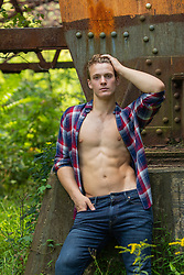 sexy man with open shirt by a train trestle