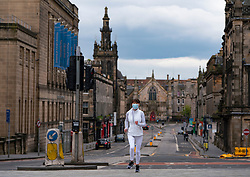Edinburgh, Scotland, UK. 29 April 2020. Views of Edinburgh Old Town as coronavirus lockdown continues in Scotland. Streets remain deserted and shops and restaurants closed and many boarded up. Scottish Government now recommends public to wear face masks. Female jogger wearing face mask runs along a deserted street. Iain Masterton/Alamy Live News