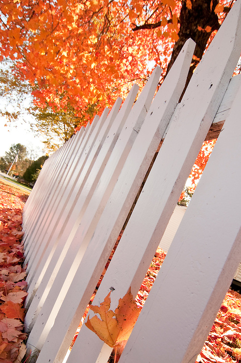 Exterior of the Nahma Inn with fall color and picket fence in Nahma Michigan.