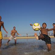 A beach scene as locals play football in the sunshine on Sao Conrado beach, Rio de Janeiro,  Brazil. 7th July 2010. Photo Tim Clayton..