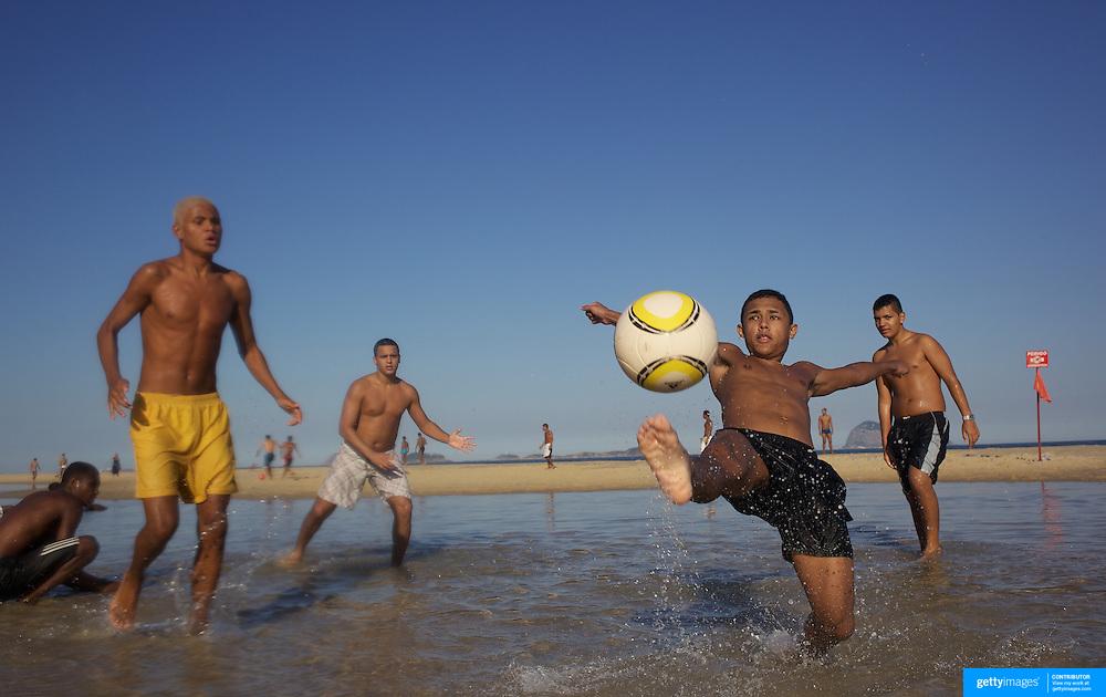 A beach scene as locals play football in the sunshine on Sao Conrado beach, Rio de Janeiro,  Brazil. 7th July 2010. Photo Tim Clayton..
