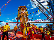"02 JUNE 2017 - SAMUT SAKHON, THAILAND: Dragon dancers get off a boat that carried them up the Tha Chin River during the procession for the City Pillar Shrine. The Chaopho Lak Mueang Procession (City Pillar Shrine Procession) is a religious festival that takes place in June in front of city hall in Samut Sakhon. The ""Chaopho Lak Mueang"" is  placed on a fishing boat and taken across the Tha Chin River from Talat Maha Chai to Tha Chalom in the area of Wat Suwannaram and then paraded through the community before returning to the temple in Samut Sakhon. Samut Sakhon is always known by its historic name of Mahachai.      PHOTO BY JACK KURTZ"