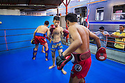 "18 DECEMBER 2104 - BANGKOK, THAILAND: Boxers work out while a commuter train goes by the Kanisorn gym. The Kanisorn boxing gym is a small gym along the Wong Wian Yai - Samut Sakhon train tracks. Young people from the nearby communities come to the gym to learn Thai boxing. Muay Thai (Muai Thai) is a Thai fighting sport that uses stand-up striking along with various clinching techniques. It is sometimes known as ""the art of eight limbs"" because it is characterized by the combined use of fists, elbows, knees, shins, being associated with a good physical preparation that makes a full-contact fighter very efficient. Muay Thai became widespread internationally in the twentieth century, when practitioners defeated notable practitioners of other martial arts. A professional league is governed by the World Muay Thai Council. Muay Thai is frequently seen as a way out of poverty for young Thais and Muay Thai camps and schools are frequently crowded. Muay Thai professionals and champions are often celebrities in Thailand.     PHOTO BY JACK KURTZ"