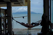 Afternoon nap in a hammock. During the building of a new hotel, construction workers  are taking a break. Photographed in fisherman village district, Koh Samui, Thailand