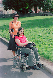 Mother pushing daughter with cerebral palsy in wheelchair,