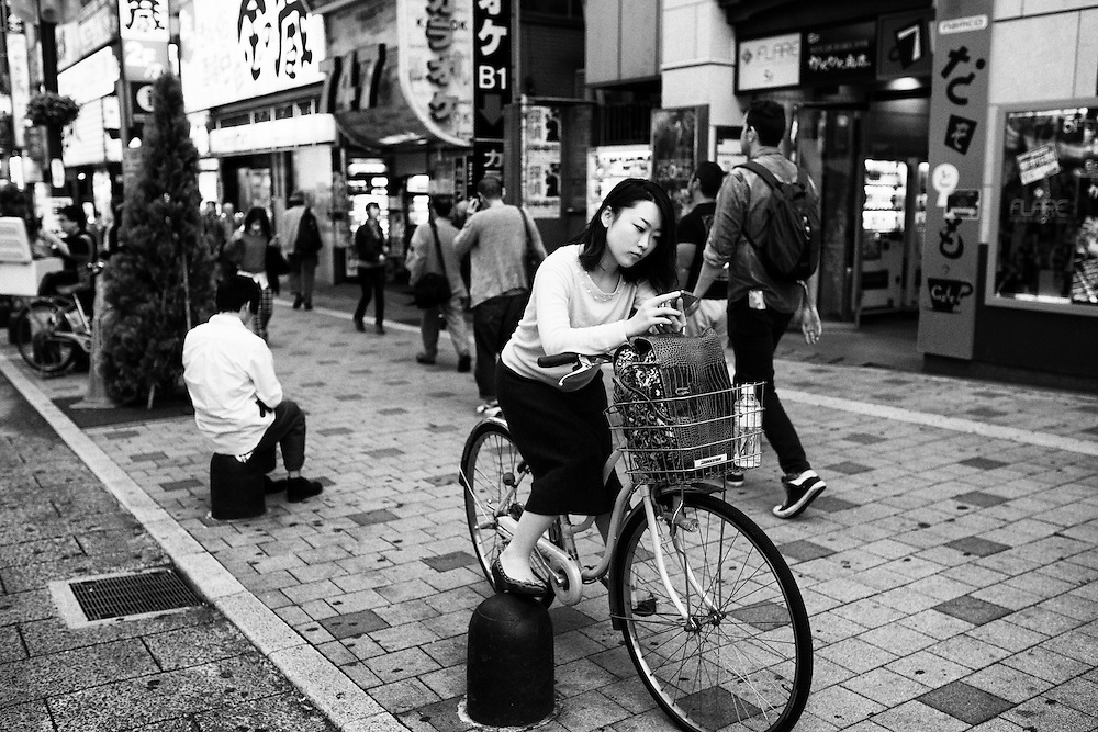 TOKYO, JAPAN - OCTOBER 20 : A woman using her mobile phone in Kabukicho, Shinjuku district Tokyo, Japan on October 20, 2015. <br /> <br /> Photo: Richard Atrero de Guzman