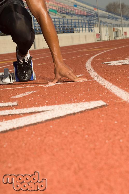 Male track athlete on starting block