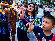 "01 MARCH 2018 - BANGKOK, THAILAND:    People light prayer candles before joining a procession around Wat Pathum Wanaram in central Bangkok. Many people go to temples to perform merit-making activities on Makha Bucha Day, which marks four important events in Buddhism: 1,250 disciples came to see the Buddha without being summoned, all of them were Arhantas, or Enlightened Ones, and all were ordained by the Buddha himself. The Buddha gave those Arhantas the principles of Buddhism. In Thailand, this teaching has been dubbed the ""Heart of Buddhism.""    PHOTO BY JACK KURTZ"