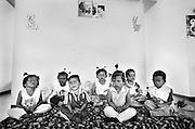 Die Kinder aus dem Haus von PAI und DAAI meditieren fuer eine Viertelstunde nach dem Kinderfest. Fuer das Kinderfest wurden sie geschminkt und die kleinen  Maedchen haben sich ihre Haare zu kleinen Zoepfchen gebunden...An der Wand rechts haengt ein Poster von Buddha. Ueber ihnen haengt das Bild vom Moench ALONGKOT TIKKAPANYO, aus dem Kloster Watpanambo, der das Sterbehospiz fuer Aids-Kranke in Lop Buri gegruendet hat.  Der Moench hat Karl Morsbach 80km von Kloster entfernt ein Stueck Land fuer das Dorf BAAN GERDA gegeben..Dahinter haengen die Bilder vom Koenig und der Koenigin Thailands.Provinz Lop Buri, Thailand..These are the children from the house of PAI and DAAI. They meditate after they came home from the childrens party. Therefor all the children have funny hairstyling and make-up on their faces..Above on the wall, at right a poster of Buddha. Above in the middle on the wall, photo of the monch ALONGKOT TIKKAPANYO, from the monastery Watpanambo. The monch gave Karl Morsbach some land to built up the village for these children. . Lop Buri, Thailand....