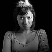 An Indian woman in a birthday hat crossing her arms and looking unhappy.