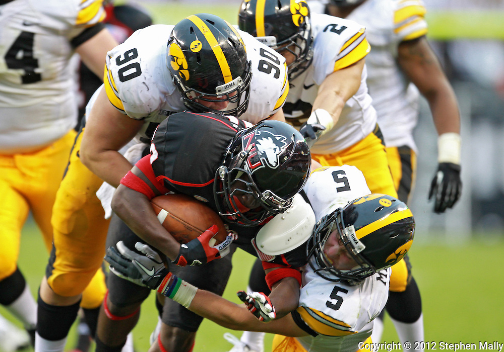 September 01 2012: Northern Illinois Huskies running back Keith Harris Jr. (20) is hit by Iowa Hawkeyes defensive lineman Louis Trinca-Pasat (90) and Iowa Hawkeyes defensive back Tanner Miller (5) during the second half of the NCAA football game between the Iowa Hawkeyes and the Northern Illinois Huskies at Soldiers Field in Chicago, Illinois on Saturday September 1, 2012. Iowa defeated Northern Illinois 18-17.