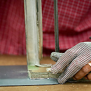 JUNE 28, 2016 --- COROZAL, PUERTO RICO<br /> Fernando Vegas wears a metal glove as he cuts fabric by hand at Bluewater Defense. The company makes pants for the US Army.<br /> (Photo by Angel Valentin/Freelance)