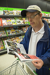 Day Service user with learning disability looking at a magazine that they have taken off the shelf in the supermarket,