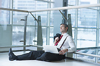 Businessman sitting on ground asleep with laptop