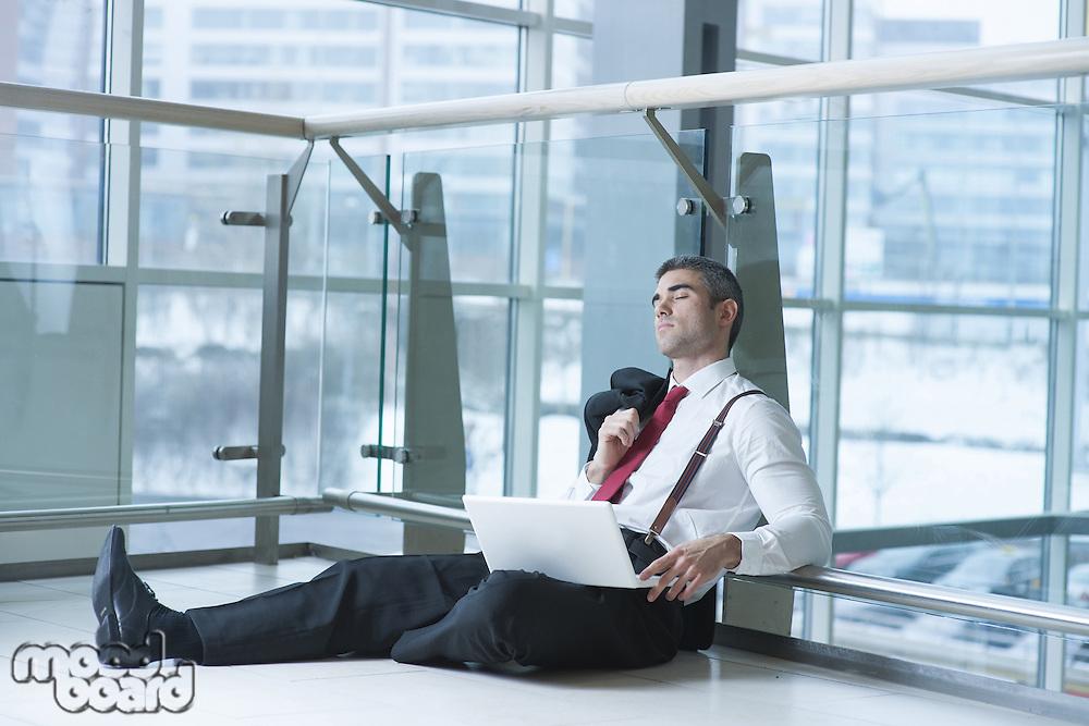 Businessman sitting on ground asleep with laptop