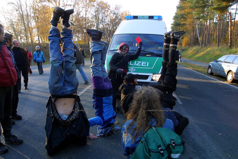 Atomkraftgegner blockieren einen Polizeiwagen, indem sie auf der Strasse Kopfstand machen