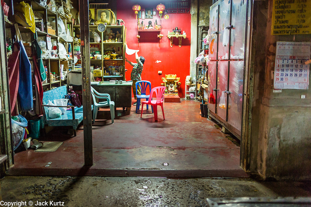 18 SEPTEMBER 2013 - BANGKOK, THAILAND: A woman closes up her home shopfront in the Chinatown section of Bangkok. Thailand in general, and Bangkok in particular, has a vibrant tradition of street food and eating on the run. In recent years, Bangkok's street food has become something of an international landmark and is being written about in glossy travel magazines and in the pages of the New York Times.      PHOTO BY JACK KURTZ
