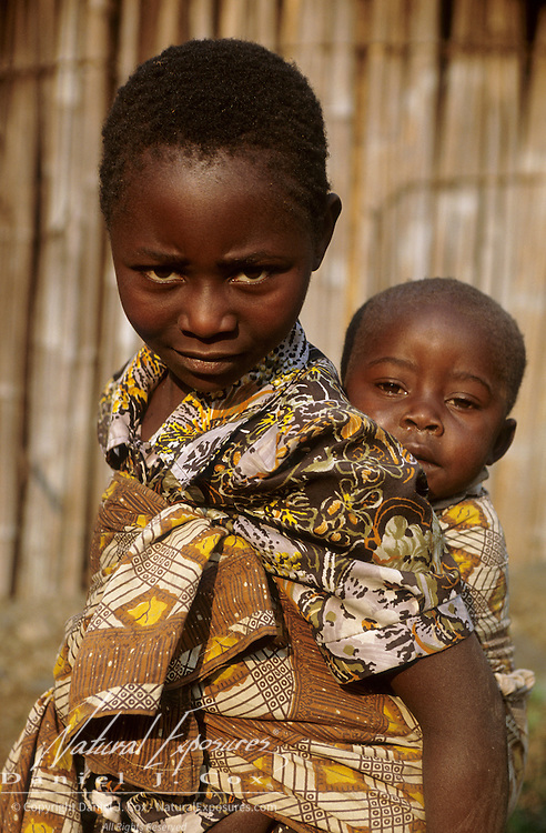 A young girl carrying her younger brother on her back in Madagascar.