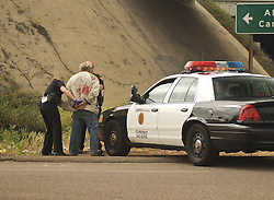 Transient man getting handcuffed by police near an overpass