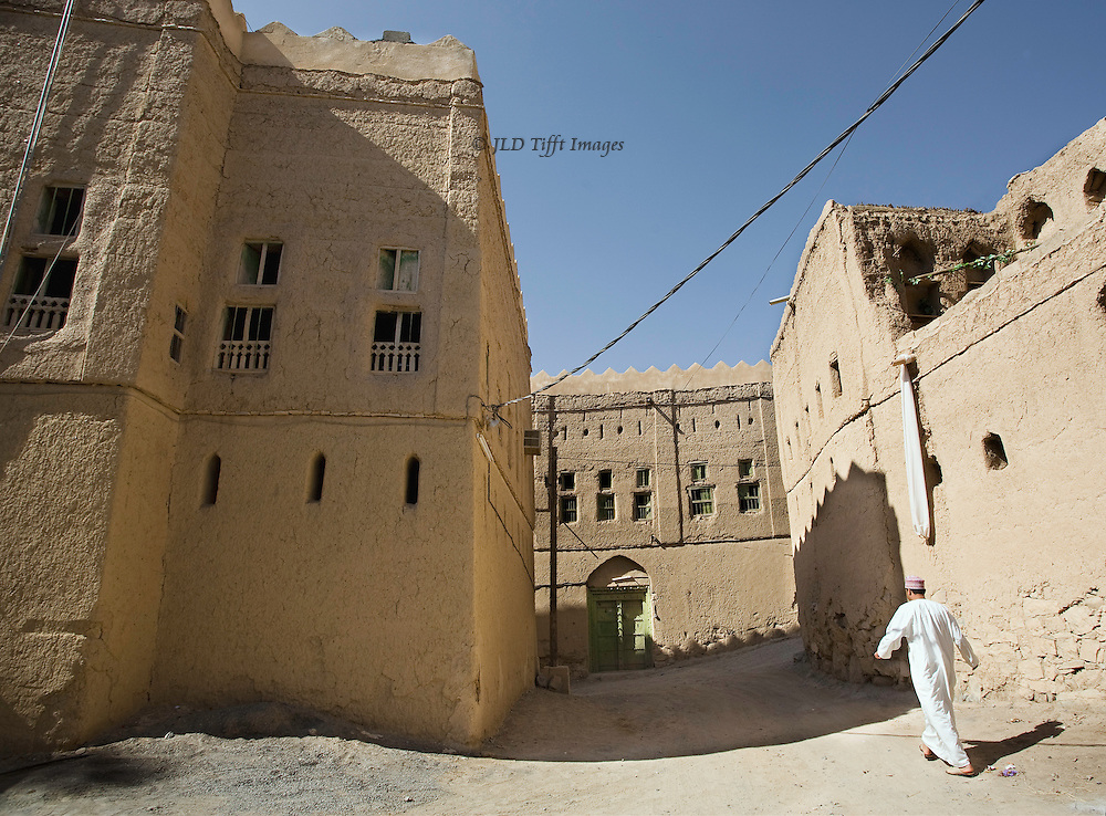 Oman, mud brick village of Al Hamra, largely abandoned.  Though some structures still endure, no restoration seems to be attempted.  Nevertheless at least some of the multistory mud brick apartment buildings are lived in and electrical wiring is strung along the street.  An Omani man in white dishdasha and embroidered traditional cap strides purposefully down the street.
