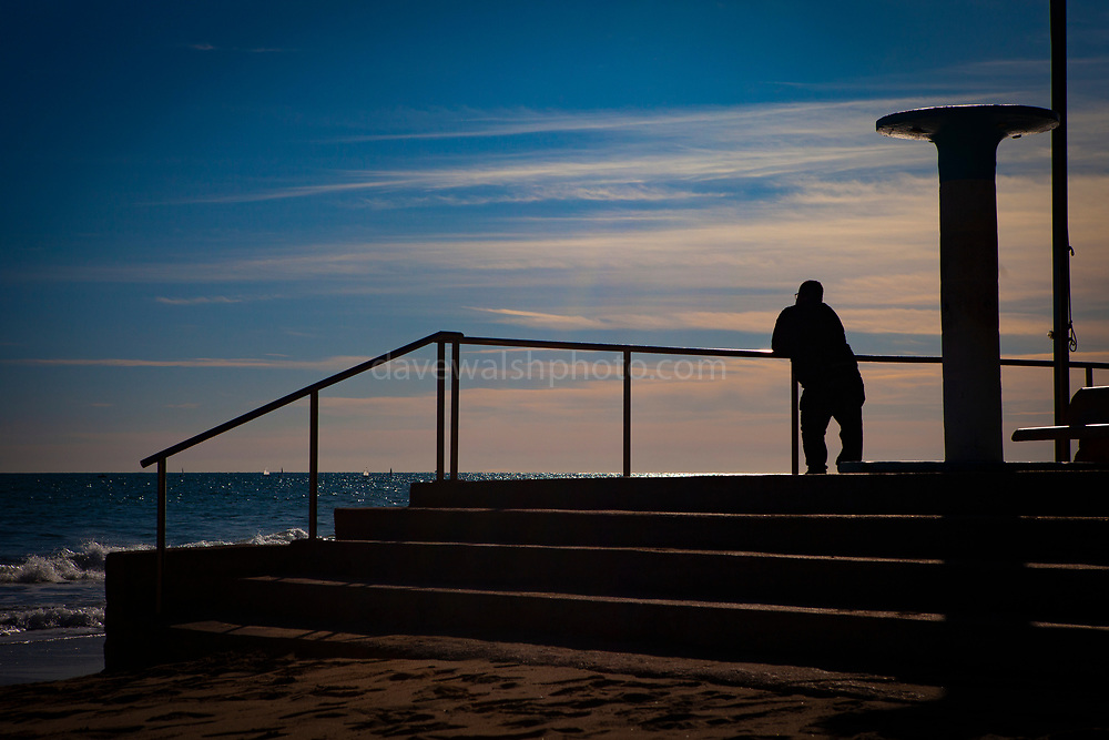 Man leaning on a rail, looking out to sea. Garraf, Barcelona, Catalonia