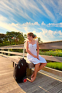 Angel sitting next to wheeled suitcase on Marsh Pier, Looking Back