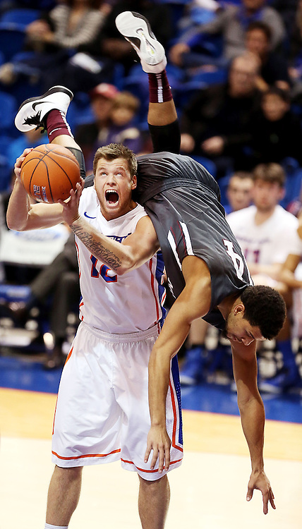 Montana mens basketball player Jermaine Edmonds Jr. (right, 14) goes heels over head while defending a shot by Boise State player Igor Hadziomerovic (left, 33) during the Broncos home opener at Taco Bell Arena.  Boise State defeated Montana 72-67. Tuesday November 18, 2014
