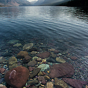 Vertical photo showing multi-colored rocks and Lake McDonald in Glacier National Park, Montana.