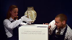 "© Licensed to London News Pictures. 28/09/2012. London, UK Auction room staff place A highly important Fatimid white-ground lustre pottery jar from Egypt dated 10th/11th century. The jar is expected to fetch 300,000-500,000GBP. Sotheby's Auction rooms in New Bond Street, London hold a photo call for their upcoming ""arts of the Islamic World"" auction which is expected to realise in the region of 5 million GBP . Photo credit : Stephen Simpson/LNP"