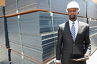 Portrait of African American male contractor holding tablet PC by stacked wooden planks