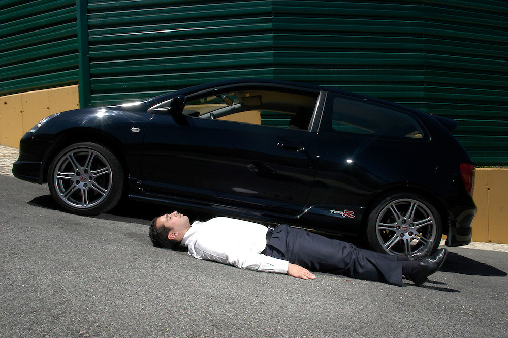 Portuguese leading art trader ad gallerist Rui Brito, playfully poses with his speedy car, 2006