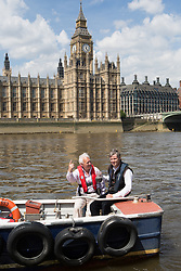 Zac Goldsmith MP introducing 10,000 eels into the River Thames. Zac Goldsmith MP (R) and Andrew Kerr (L) Chairman of Sustainable Eel Group, release several thousands eels from a boat into the Thames in front of the Houses of Parliament to publicise conservation mission to relocate more than 90 million critically endangered European eels. River Thames, Westminster, United Kingdom. Monday, 19th May 2014. Picture by Daniel Leal-Olivas / i-Images