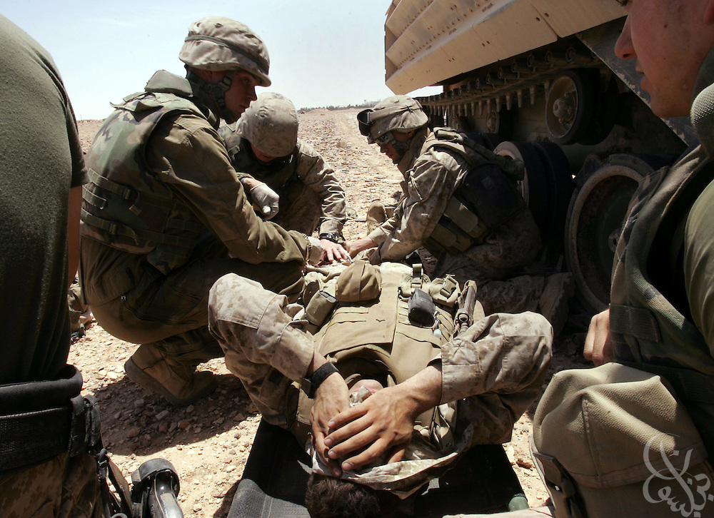 A U.S. Regimental Combat Team 2 Marine is treated for a gunshot wound on a desert road near the Syrian border during a routine mission to a radio communication tower and back May 18, 2005 near the Iraqi city of Al-Qaim.