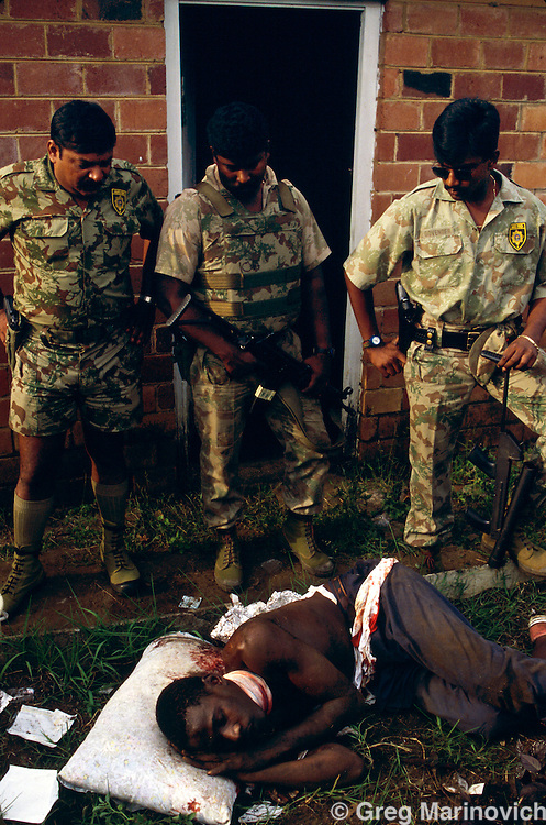 Dube, Soweto, 1994, South Africa: Riot police look down at a man they had treated who had been wounded in a train subway in Soweto. 1994.
