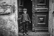 Boy standing in a house entrance in Zizkov.