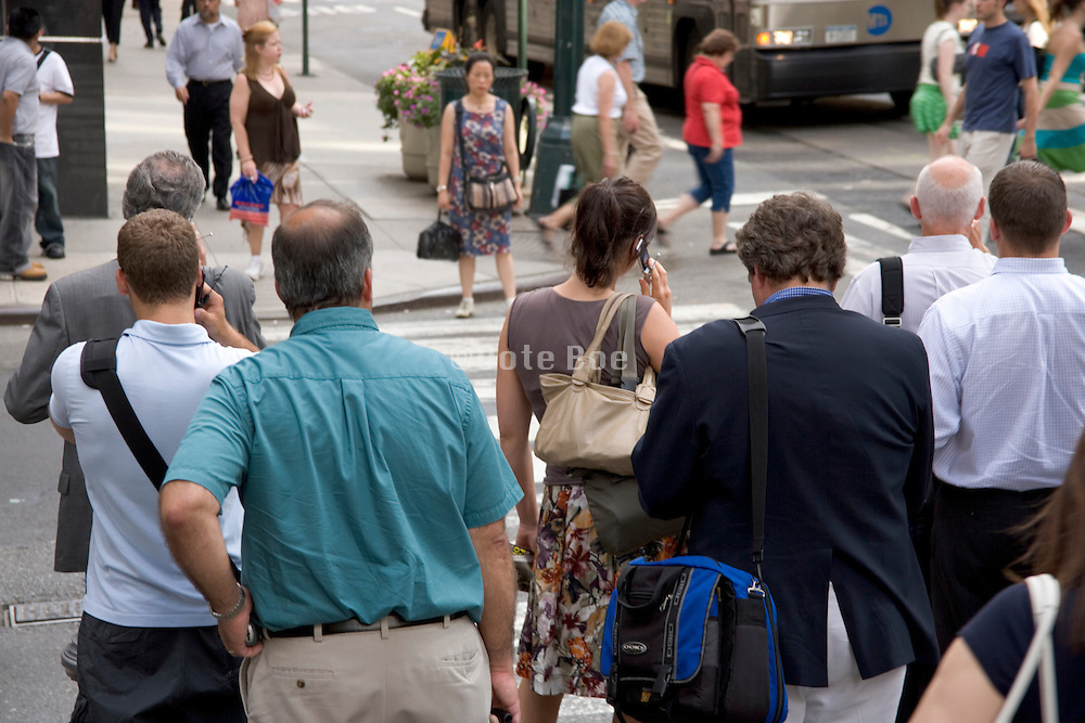 tourists and business people waiting at a red light to cross a street in New York City