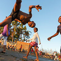 Madagascar, Tulear, Young boys laugh while performing gymnastic leaps on beach at sunset