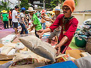 "07 AUGUST 2014 - BANGKOK, THAILAND:       Volunteers stacks sacks of rice before a food distribution program started at Pek Leng Keng Mangkorn Khiew Shrine in Bangkok. Thousands of people lined up for food distribution at the Pek Leng Keng Mangkorn Khiew Shrine in the Khlong Toei section of Bangkok Thursday. Khlong Toei is one of the poorest sections of Bangkok. The seventh month of the Chinese Lunar calendar is called ""Ghost Month"" during which ghosts and spirits, including those of the deceased ancestors, come out from the lower realm. It is common for Chinese people to make merit during the month by burning ""hell money"" and presenting food to the ghosts. At Chinese temples in Thailand, it is also customary to give food to the poorer people in the community.  PHOTO BY JACK KURTZ"